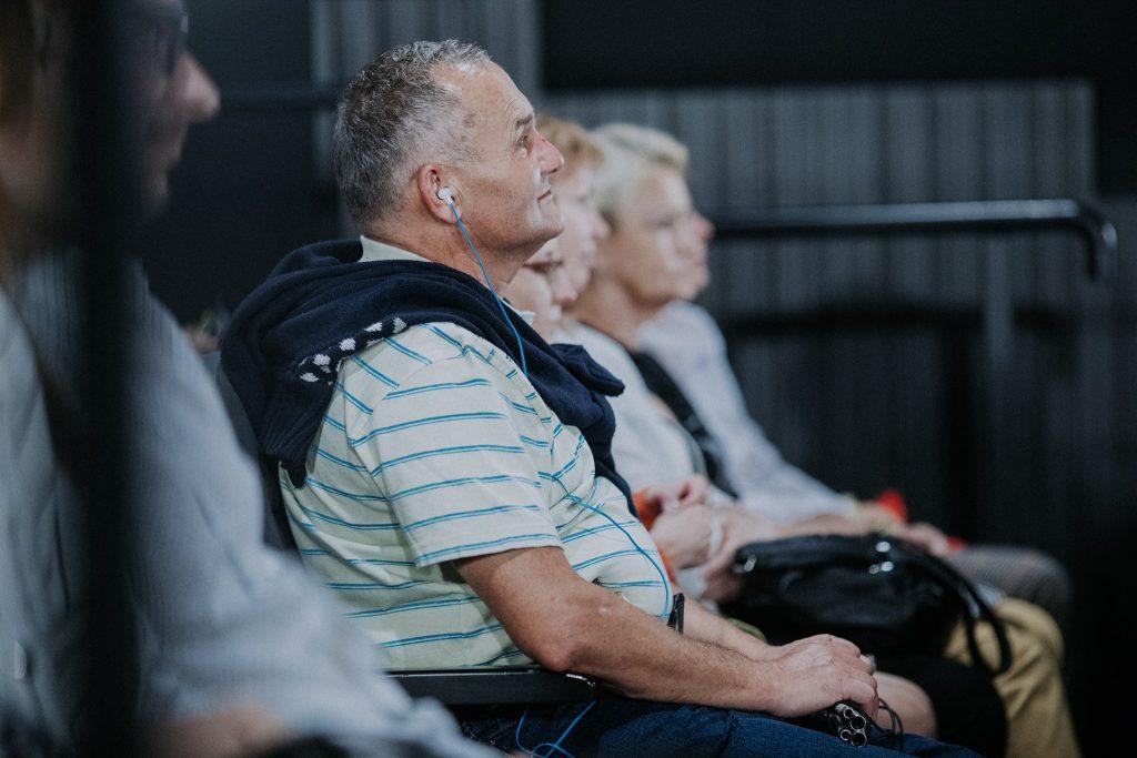 Niewidomy mężczyzna z słuchawką w uchu siedzi wśród kilku innych niewidomych osób