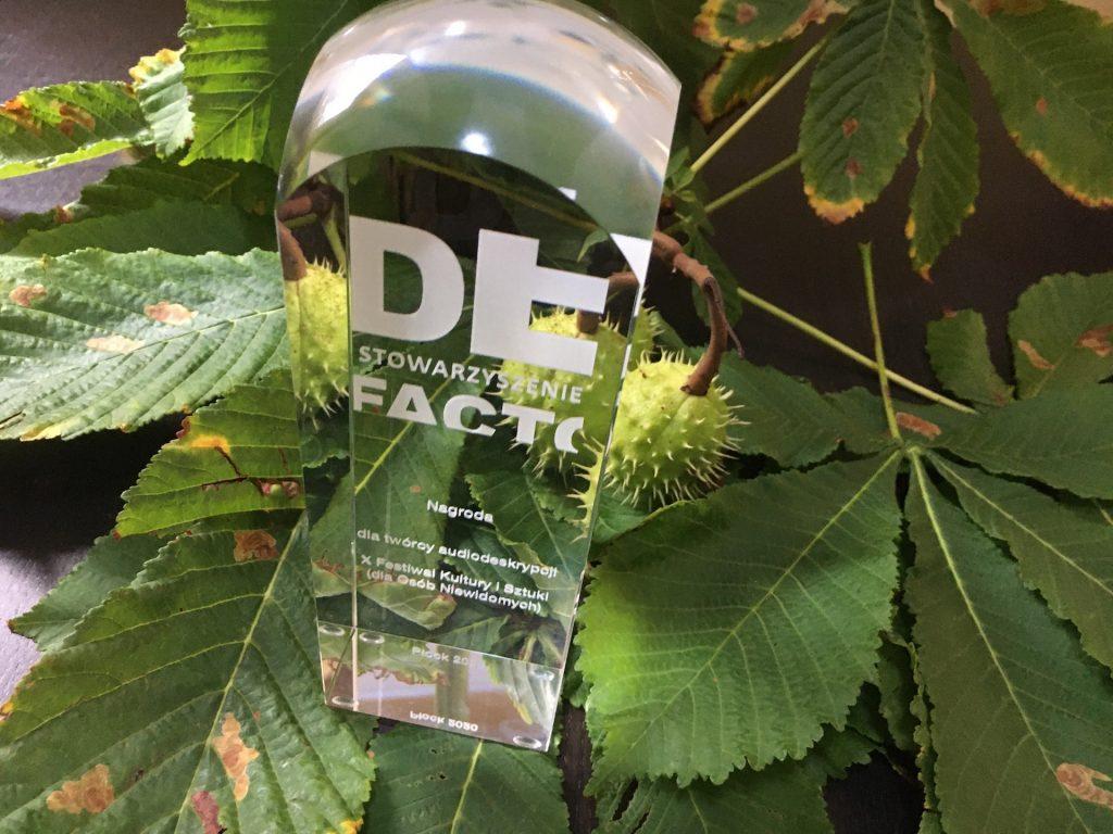 Na tle zielonych liści stoi szklana statuetka - nagroda dla twórcy najlepszej audiodeskrypcji filmowej na festiwalu