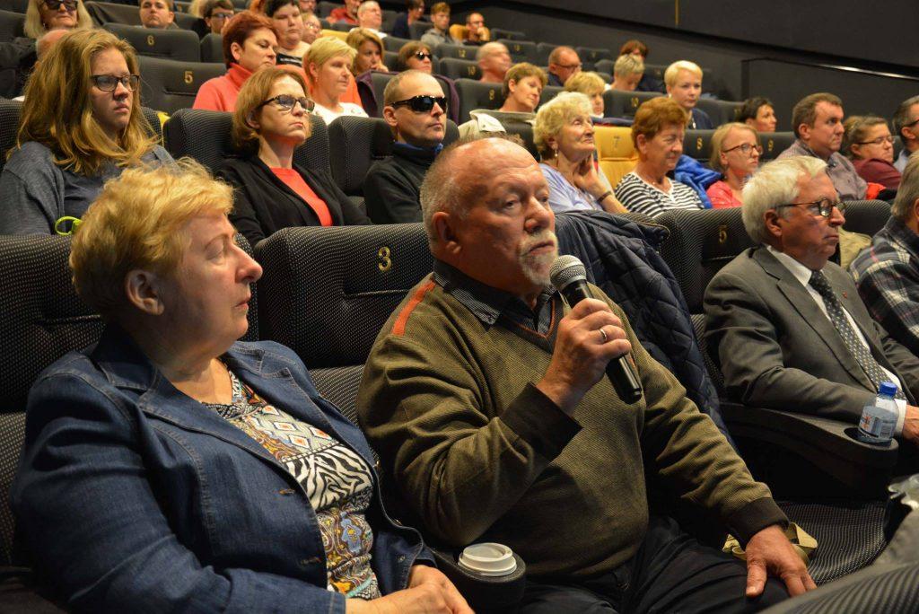Widzowie w kinie podczas dyskusji. Starszy mężczyzna trzyma w ręku mikrofon.