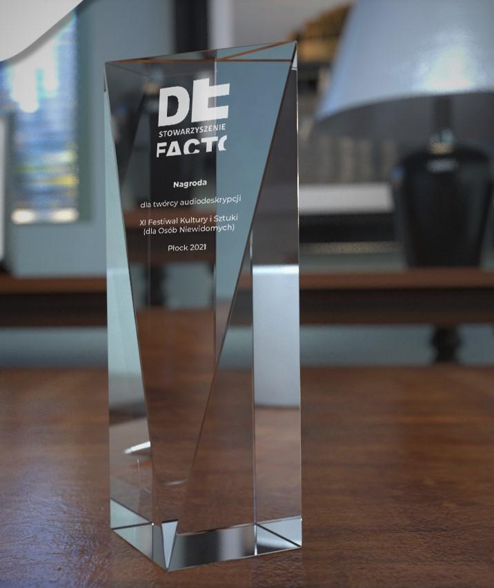 Statuetka - nagroda dla twórcy najlepszej audiodeskrypcji - szklana bryła z wygrawerowanym pamiątkowym napisem