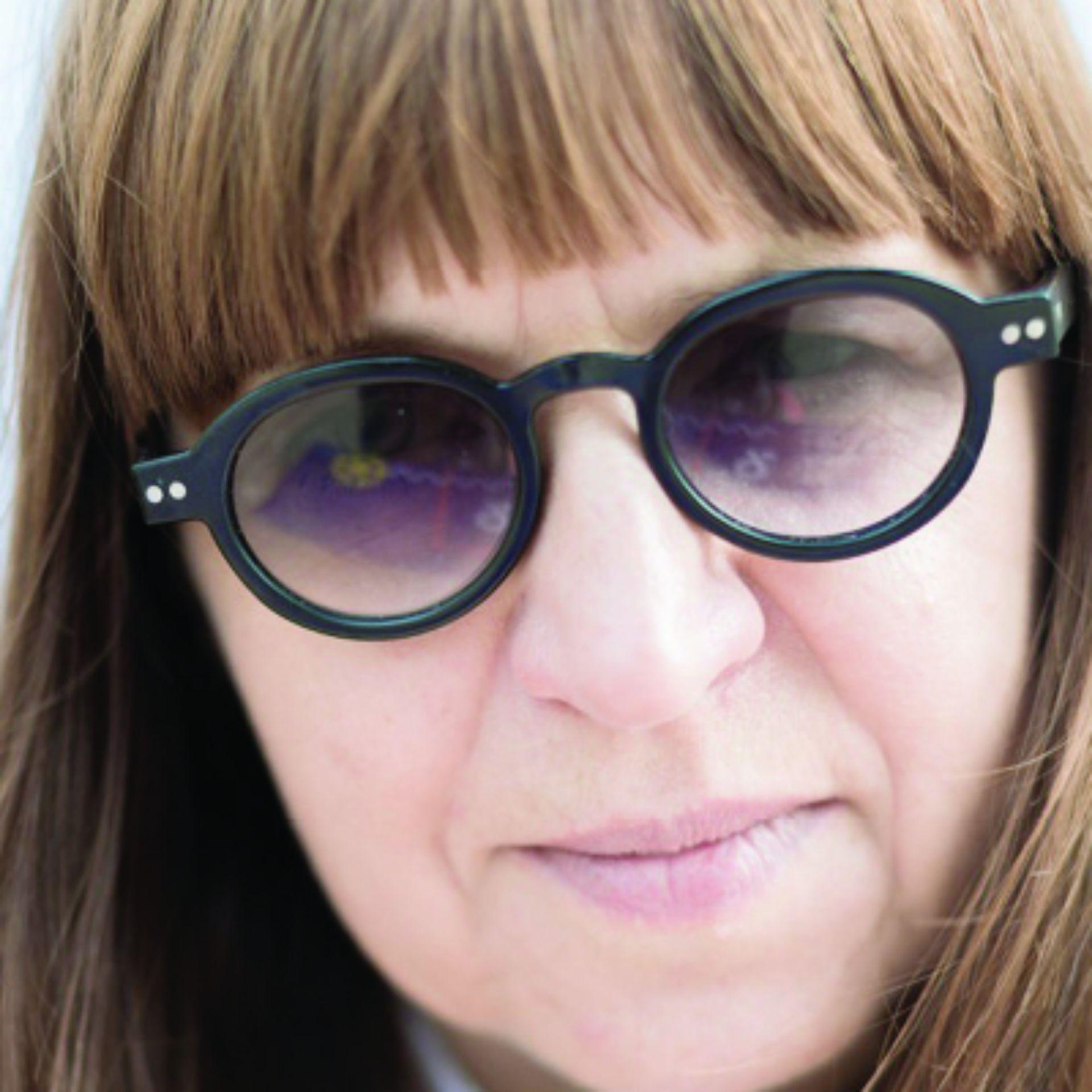 Zbliżenie na twarz kobiety w okularach i okrągłych, plastikowych, dość grubych oprawkach. Równo przycięta  grzywka opadająca na czoło. Włosy proste, ciemny blond.